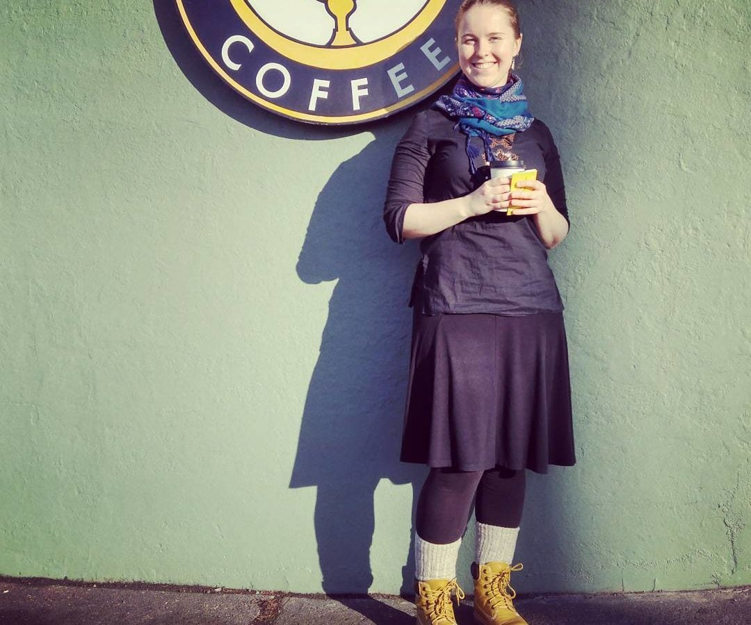 "This is a photo of Olivia with her light blonde hair pulled back, and standing outside against a green wall with the yellow and black ""Discovery Coffee"" sign. She is wearing black leggings, skirt, and top with a teal blue scarf and yellowish brown boots. She is holding a coffee."