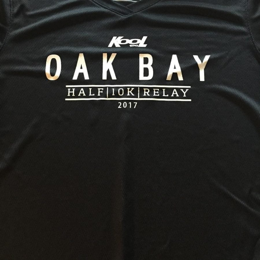 "This is a photo of the front of a black t-shirt with ""oak bay half/10km/relay 2017"" printed in white lettering on the front."