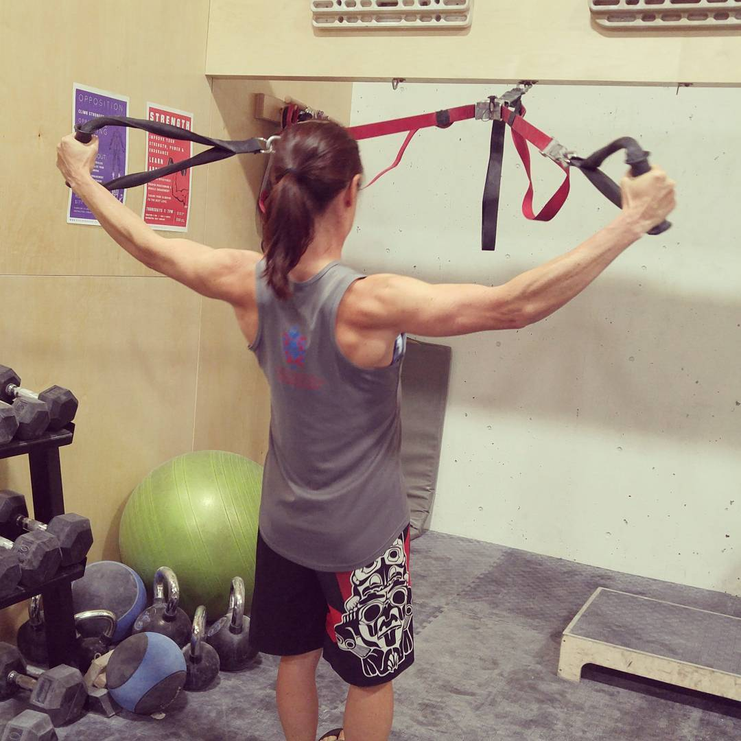 This is a photo of Christy in a brown ponytail with grey tank top and black shorts. She is facing away from us towards a wall and pulling herself up using two red and black exercise bands, which are attached to the wall. The muscles in her arms are very defined.