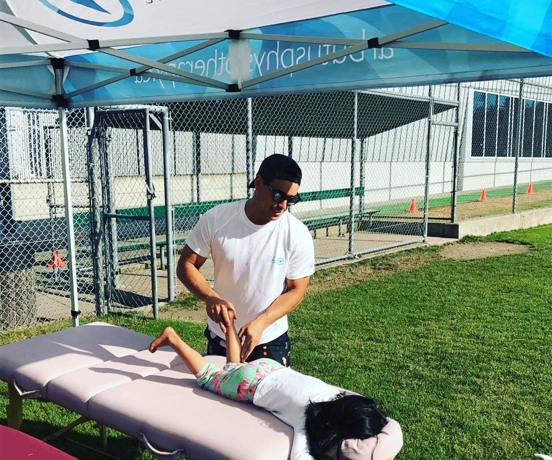 This is a photo of a man in a while t-shirt massaging the legs of a young athlete who is lying face down on the massage bed. They are outside under a white and light blue tent. It looks like a warm day.