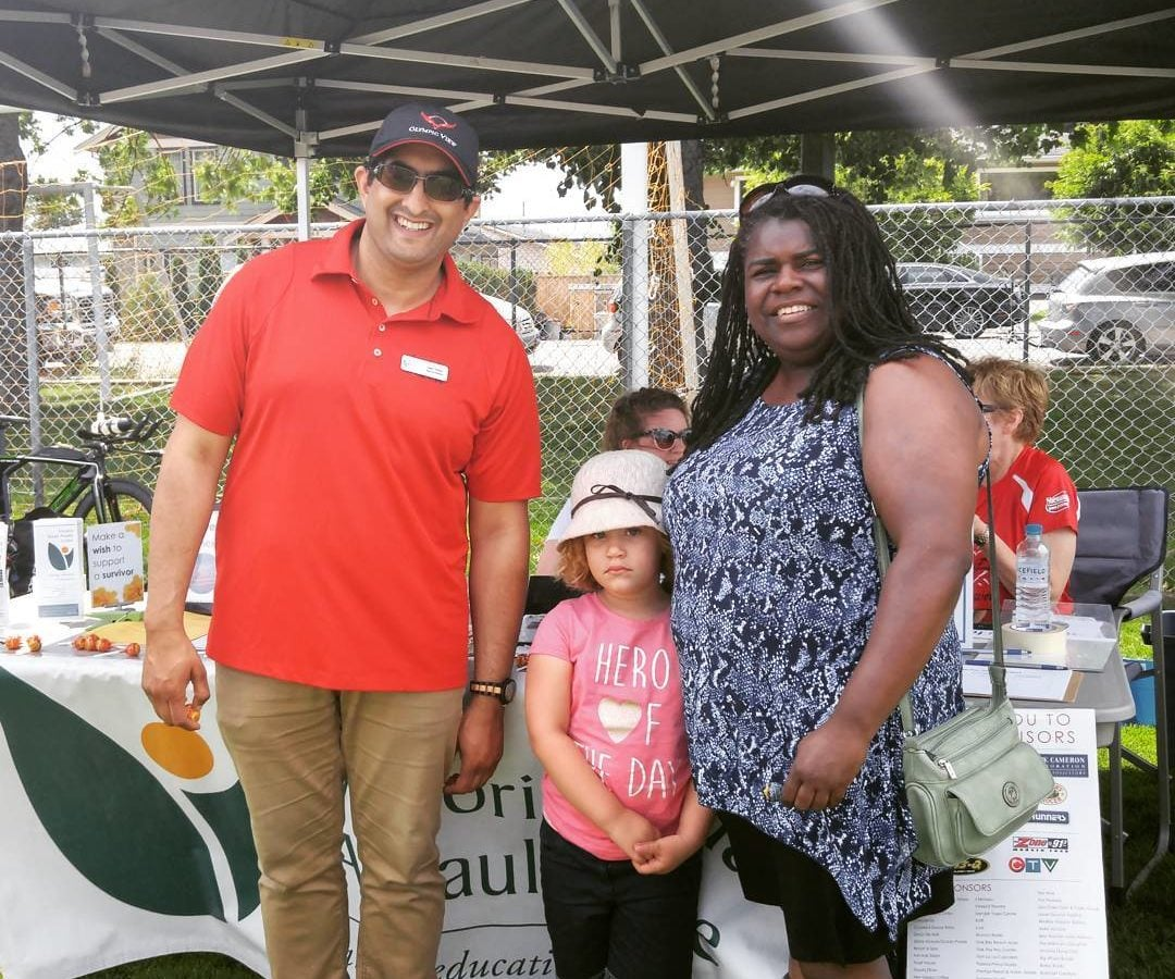 This is a photo with a smiling man on the left in a red shirt and black cap smiling, and a little girl with a pink shirt in the middle looking shy and tucking in against the woman on the right who is wearing a long black and white shirt with black shorts and also smiling.