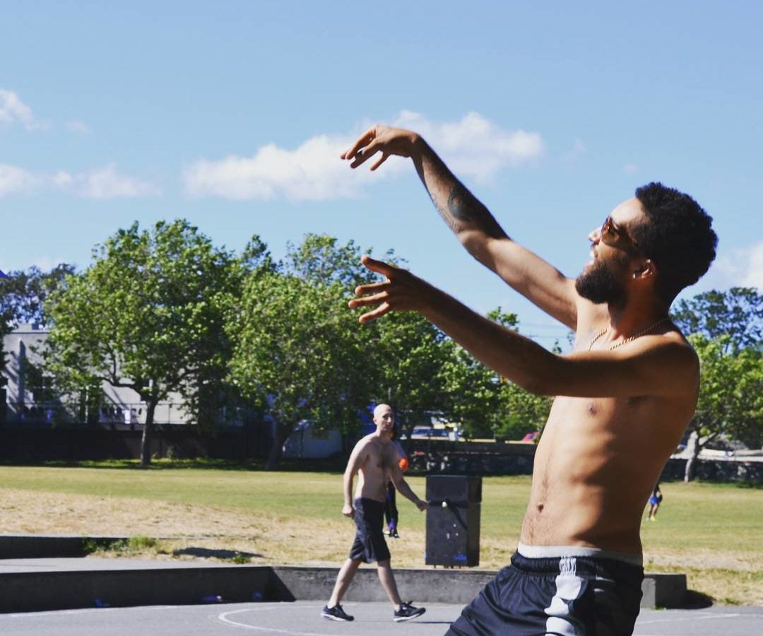 This is a photo of a man with a beard and sunglasses having just thrown a basket ball which is not in the photo. His arms are still raised having just released the ball, and he is leaning back. He is shirtless and in black shorts. It is a clear, sunny day.