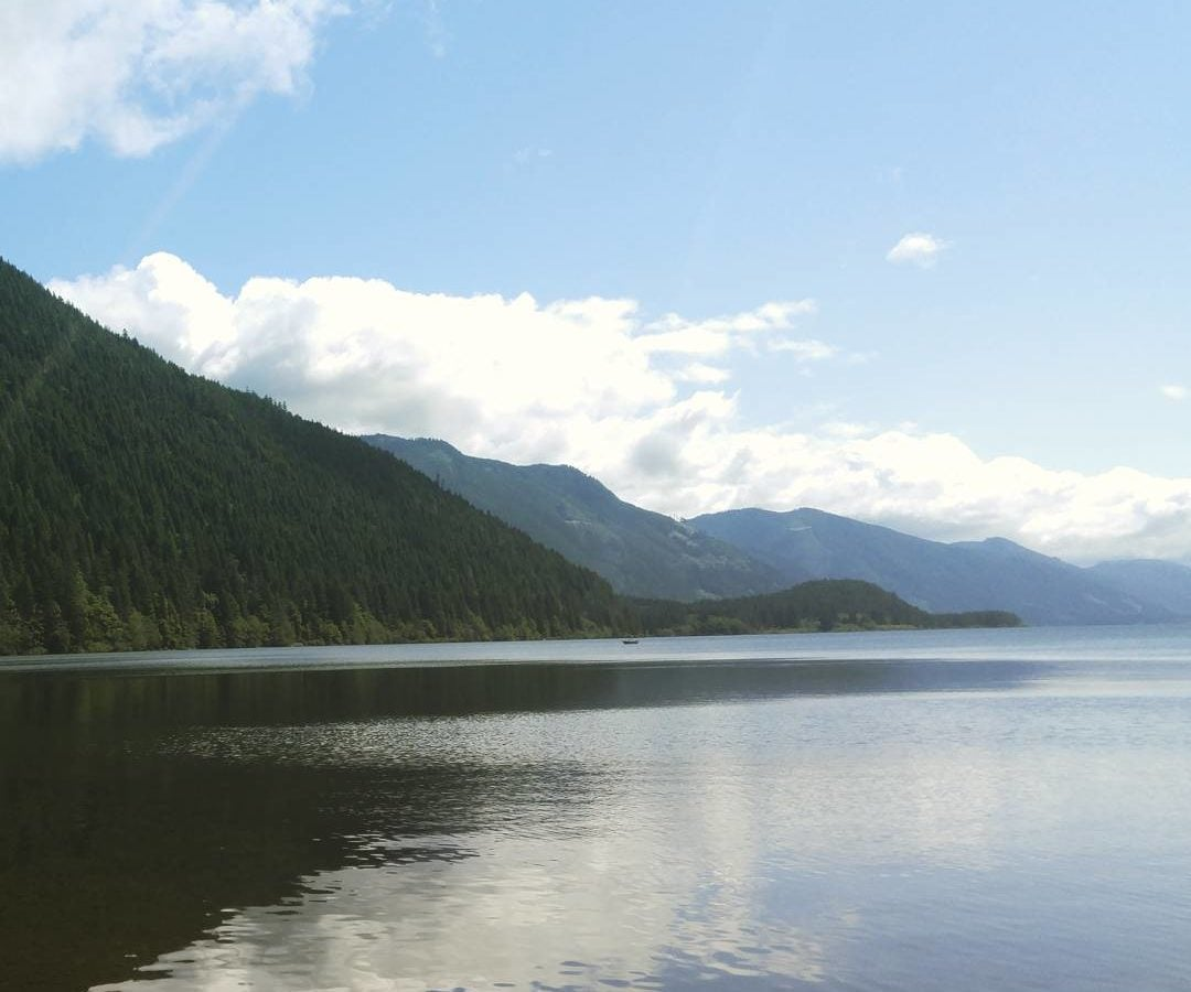 This is an image of Cowichan lake with clear, still water. The sky is blue with white fluffy clouds and been hills to the left.