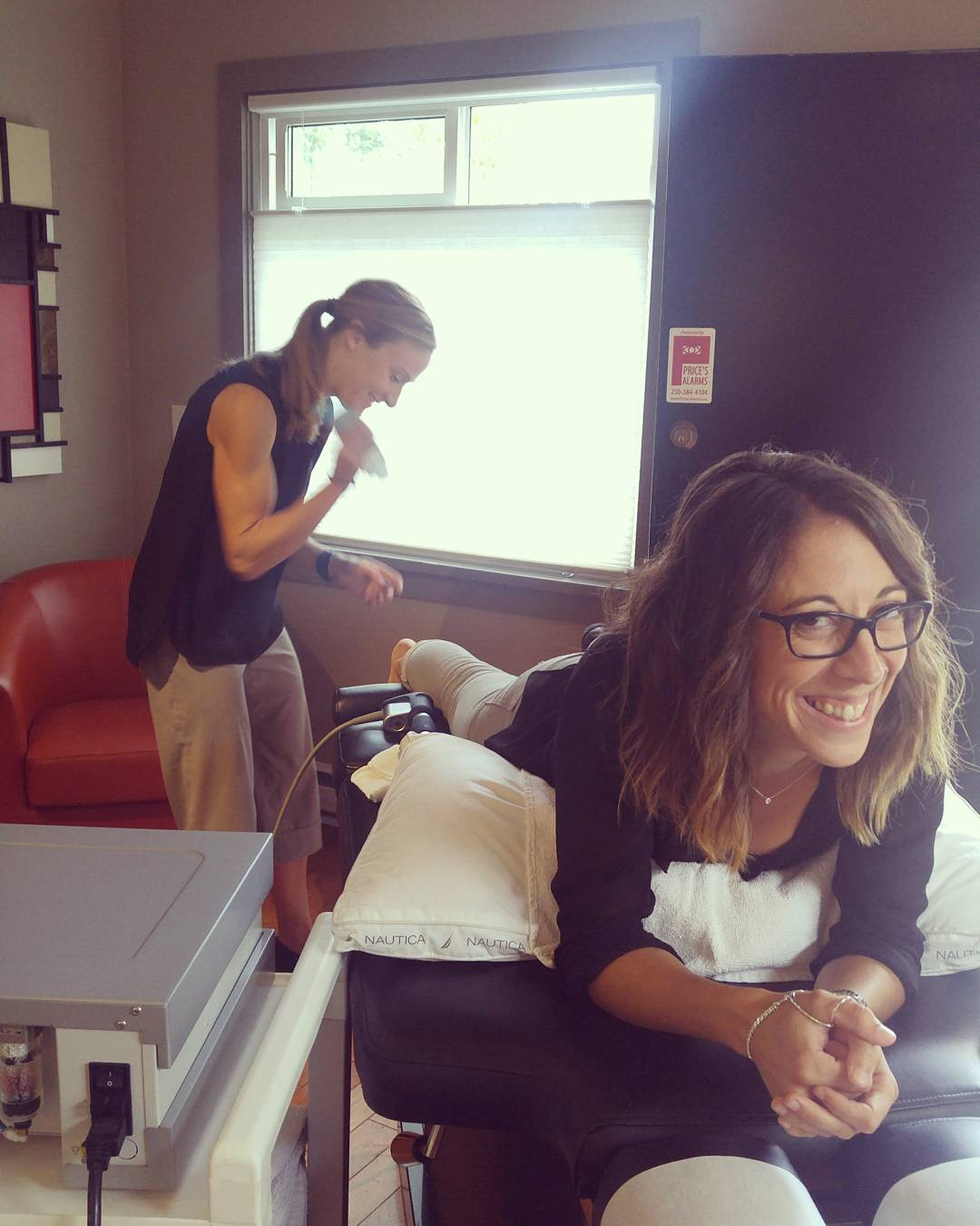 This is a photo of a woman with shoulder length brown hair smiling and lying on her stomach on a narrow bed while another woman with her hair pulled back treats her ankle.