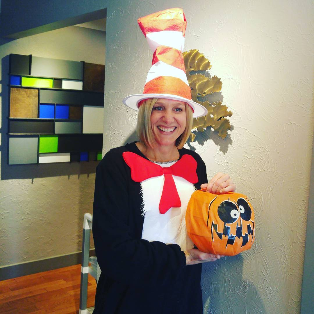 This is a photo of a blond female in a cat in the hat costume with an orange pumpkin candy basket being held in both her hands in front of her.