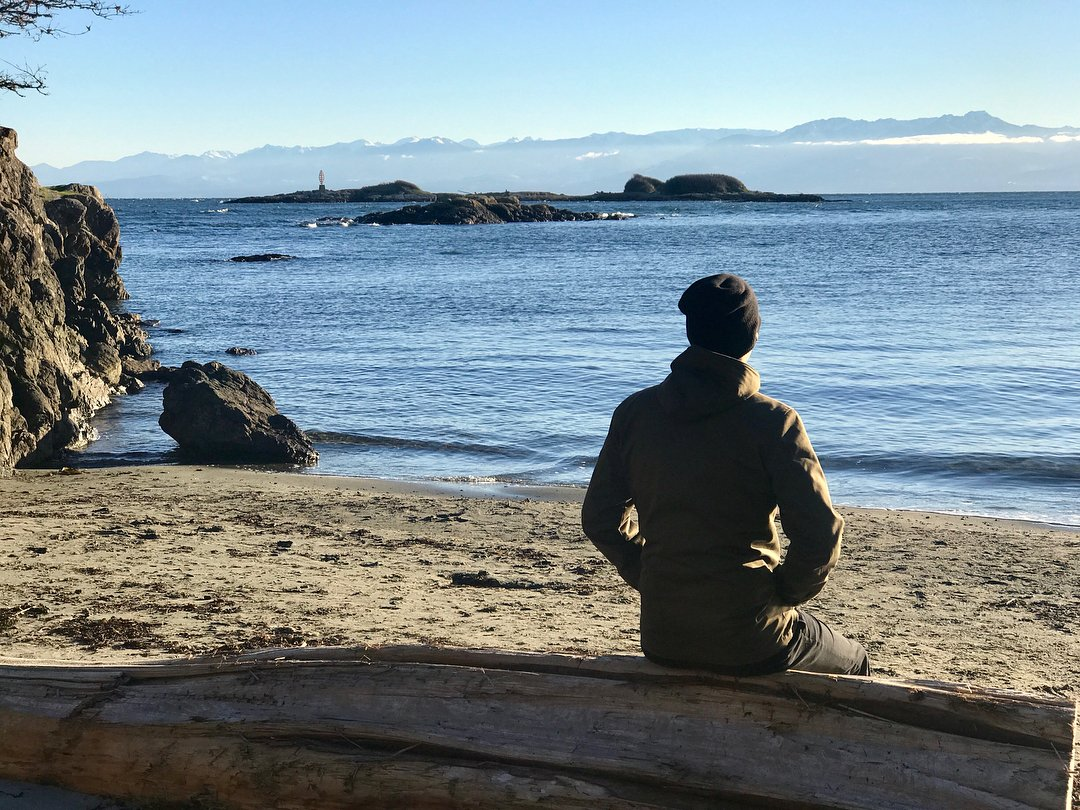 Scott Holden sits on the sunny winter beach staring at the Olympic Mountains.
