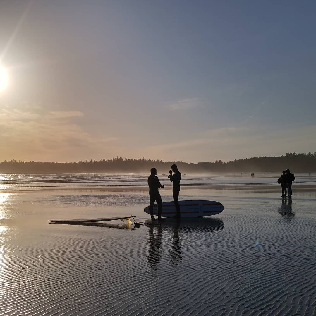 This is a photo of three figures on a beach with the sun coming from behind them so they are just silhouettes. One of the people in the distance is carrying a surf board, and two in the middle ground are standing in front of a board that's stuck in the sand with another beside them lying flat.