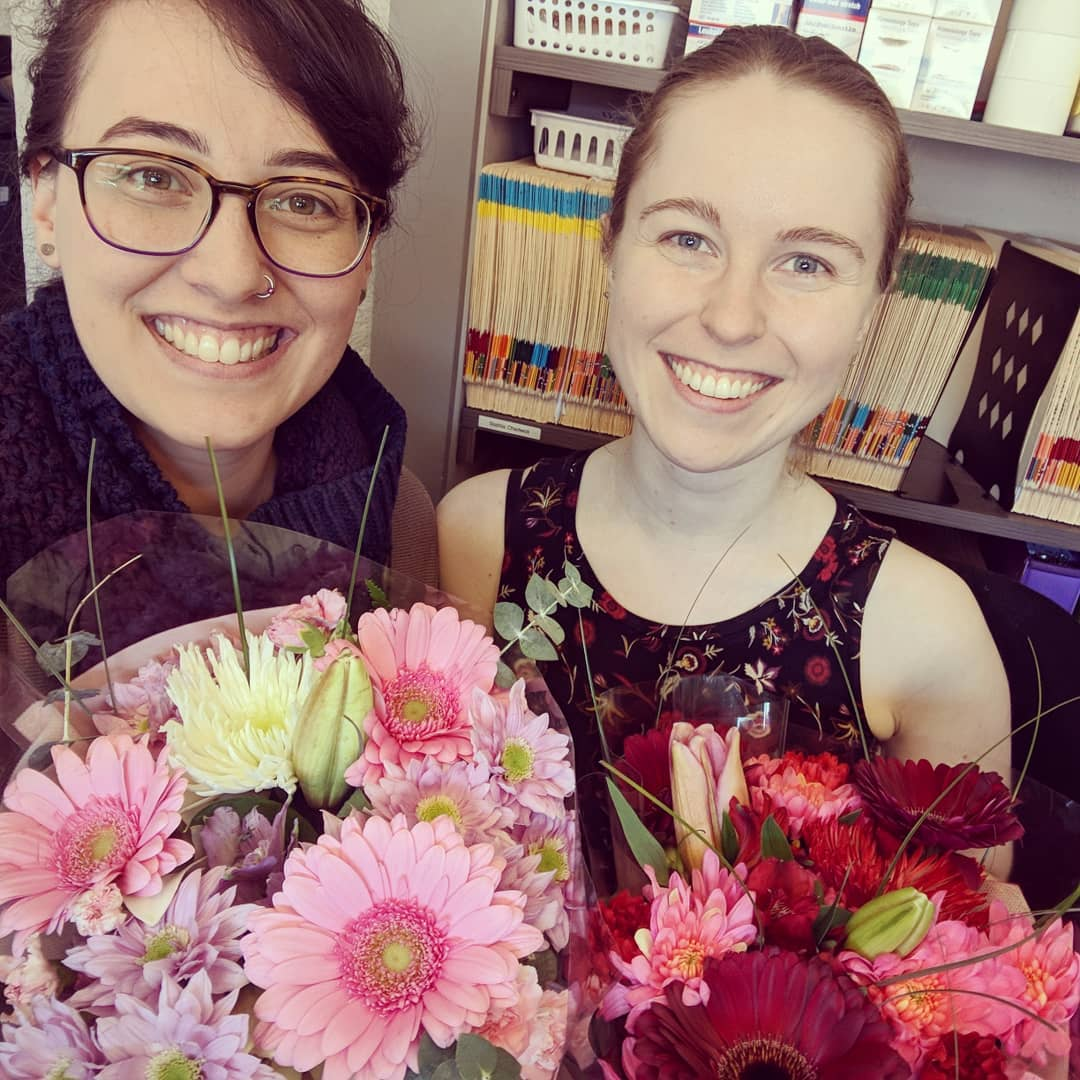 This is an image of two smiling women with brown hair who are both holding bundles of pink flowers. They are in an office