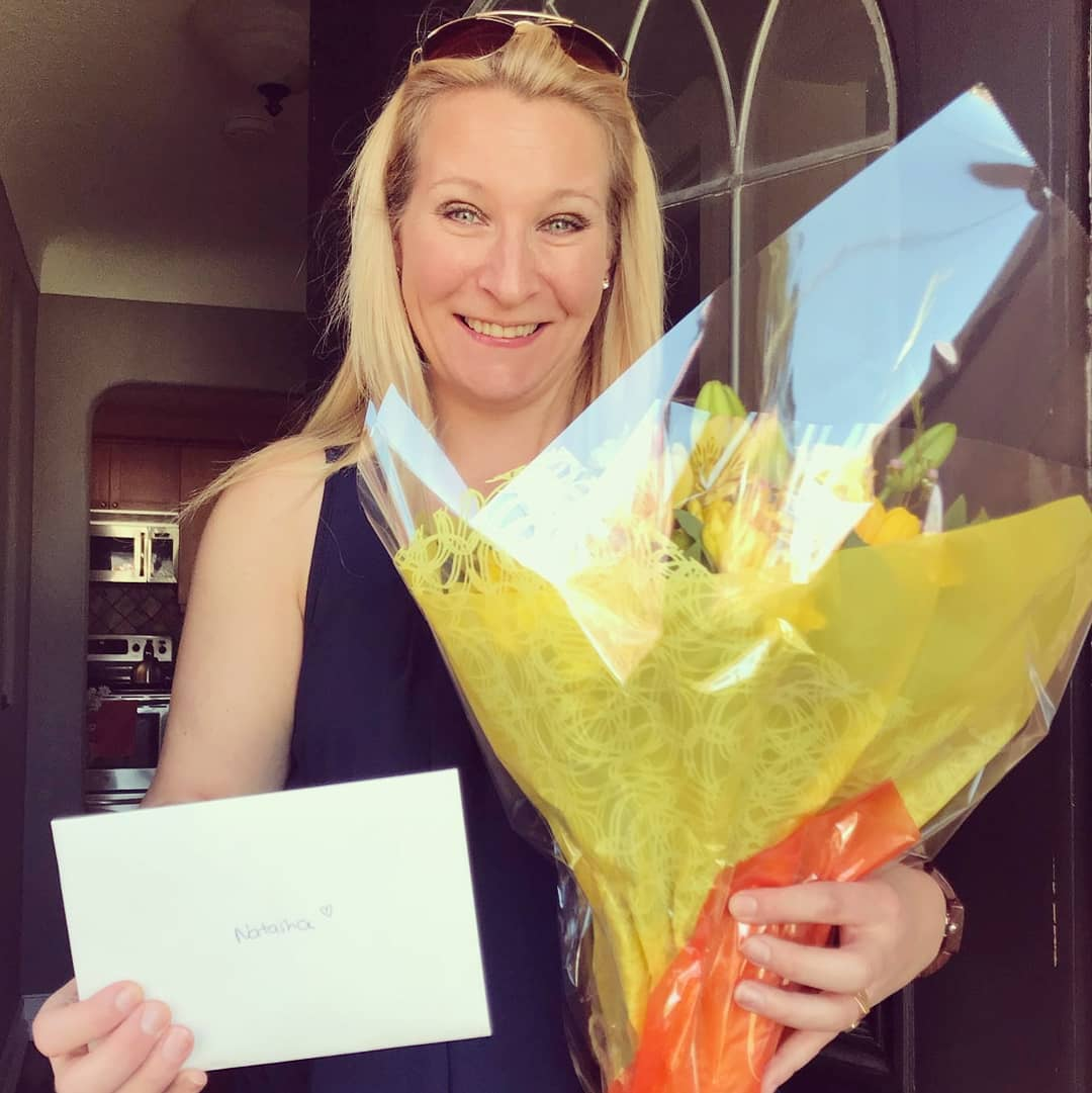 This is a photo of a blonde woman smiling and holding a bundle of flowers wrapped in yellow and orange in her left hand and a white card in her right hand.