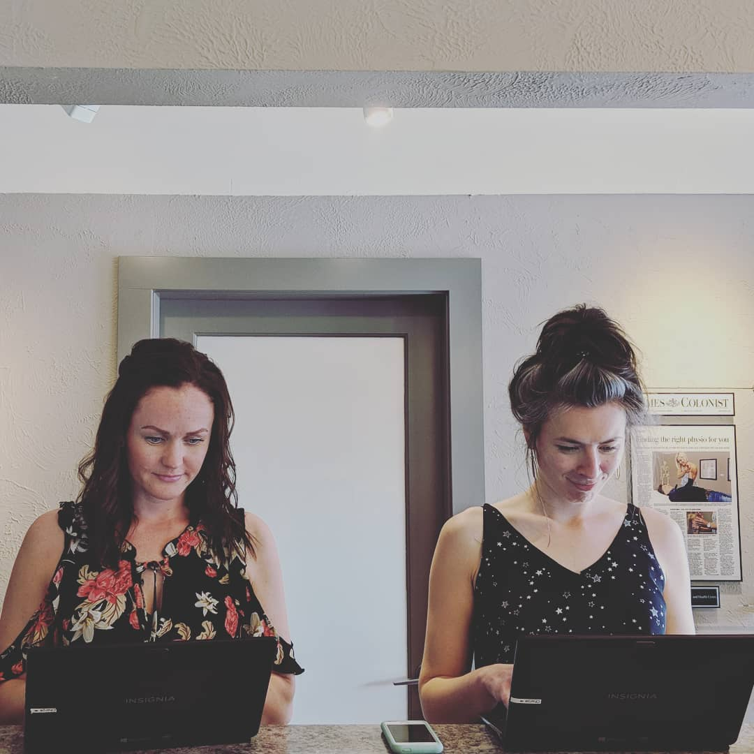 This is a photo of two women working behind black laptops in a light grey office, and both have the corners of their lips turned up in smirks.