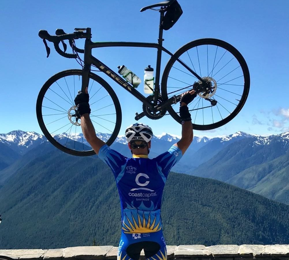 Jay Krieger holds his bike over his head on the Malahat pass as part of the Tour de Rock.
