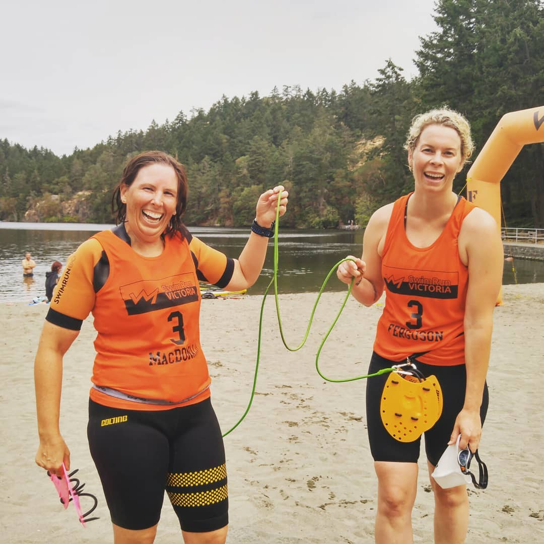 Two racers cross the finish line connected by a cord on the beach at Thetis Lake.