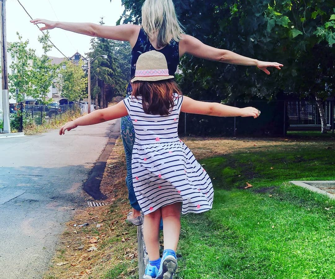 Mom and daughter balance on a beam