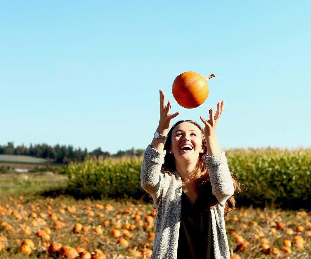 Taelor throws a pumpkin into the air, with a field of pumpkins in the background.