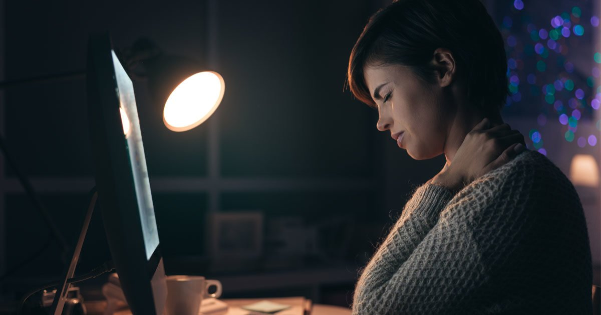 A woman rubs her neck late at night while staring into her computer
