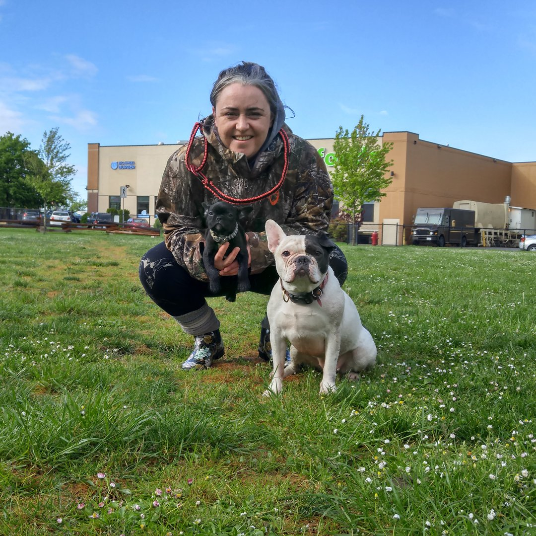 A smiling woman crouches on a field, holding a tiny puppy with another dog in the foreground; in a park in Vicwest.