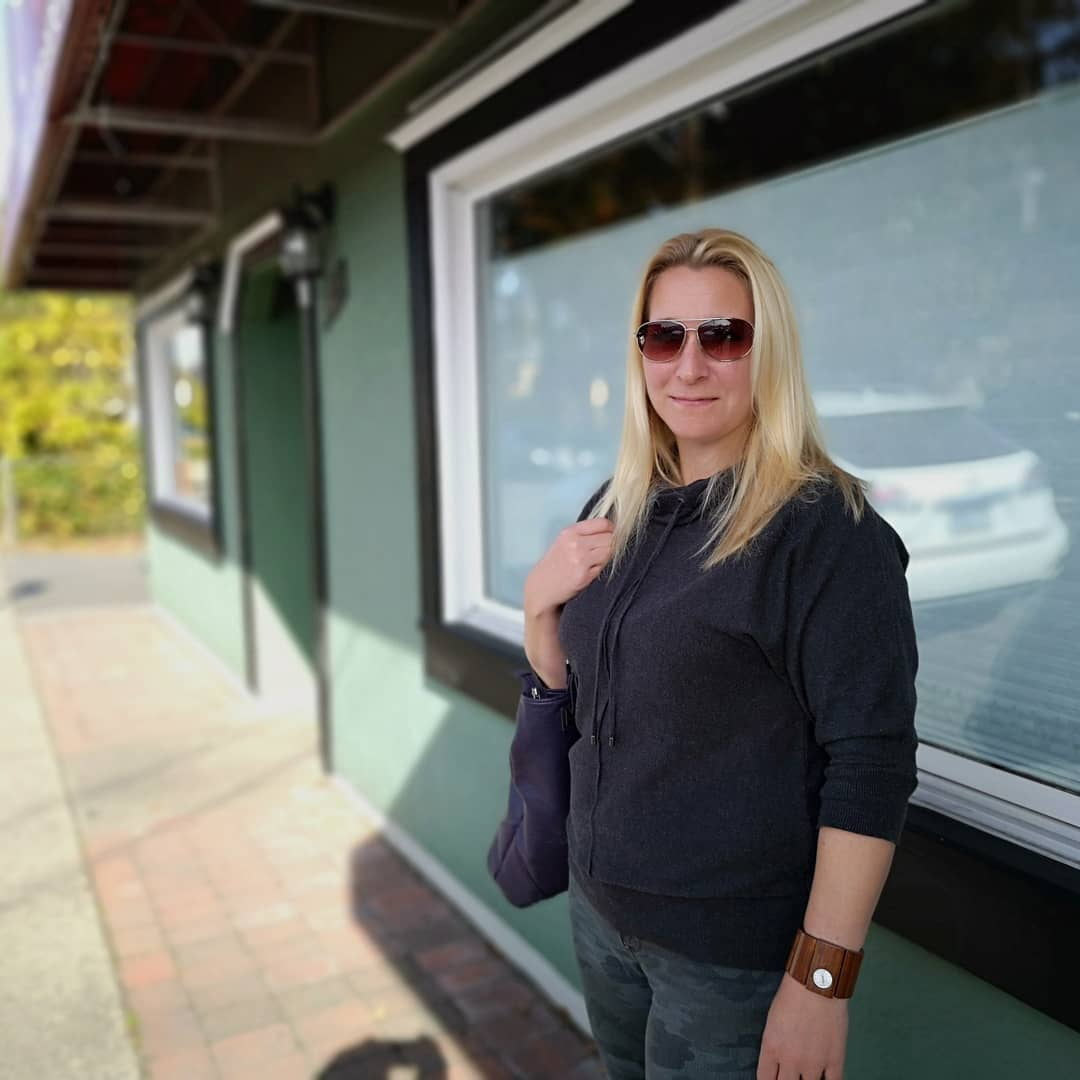 Natasha wears sunglasses on a bright day, standing in some shade in front of the clinic.