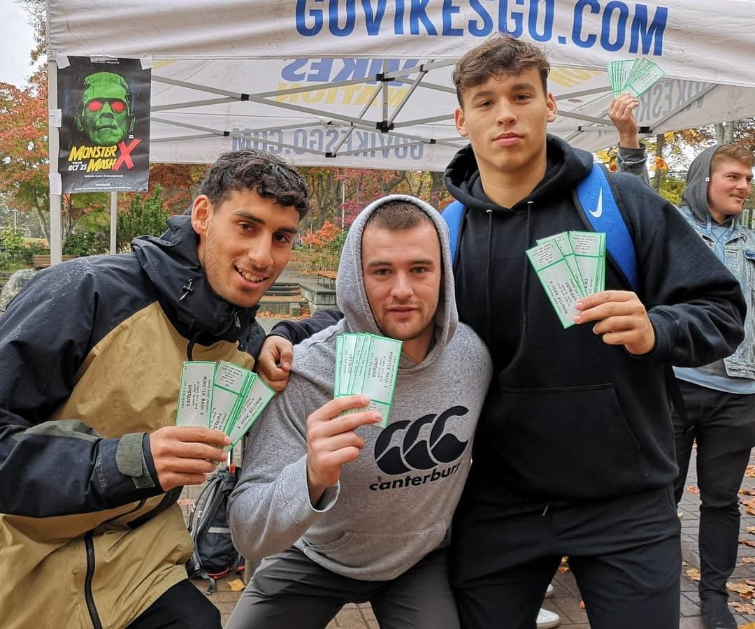 "Three UVic men's rugby players pose holding event tickets in front of a tent with a ""Go Vikes Go"" sign."