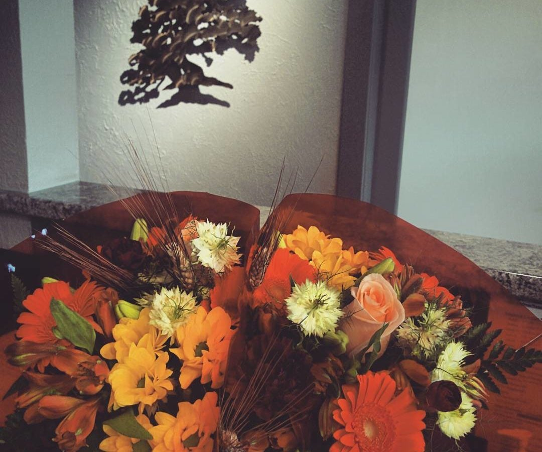 Two fall bouquets in the office, with many warm orange and brown hues.