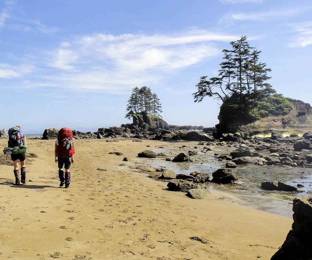 Two women hike along a sandy beach on the west coast trail, with stunning rock and tree formations along the shore.