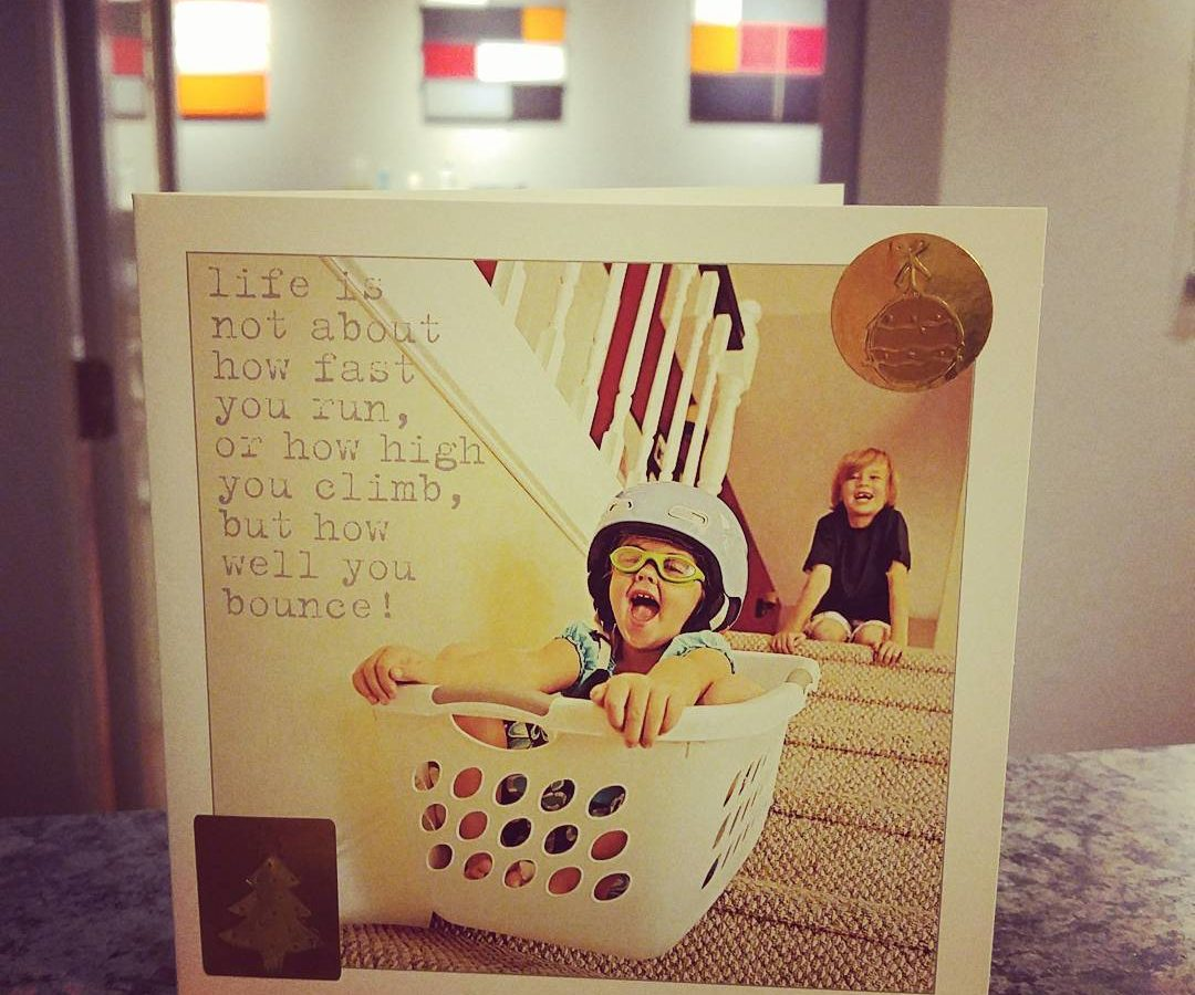 "A holiday card from a client that reads ""it's not about how fast you run or how high you climb, but how well you bounce!"" with a photo of a child sliding down stairs in a laundry basket."