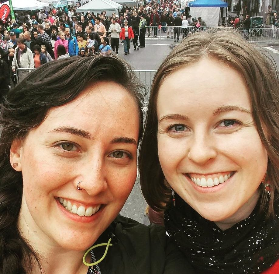 A smiling selfie taken by Mae and Olivia outside at carfreeday Victoria, with crowds of people visible in the background.