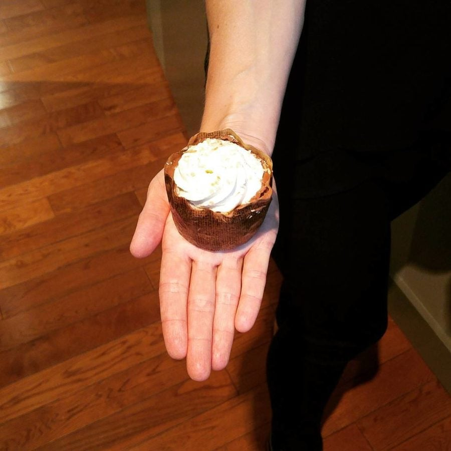 A hand holding a cupcake with white frosting.