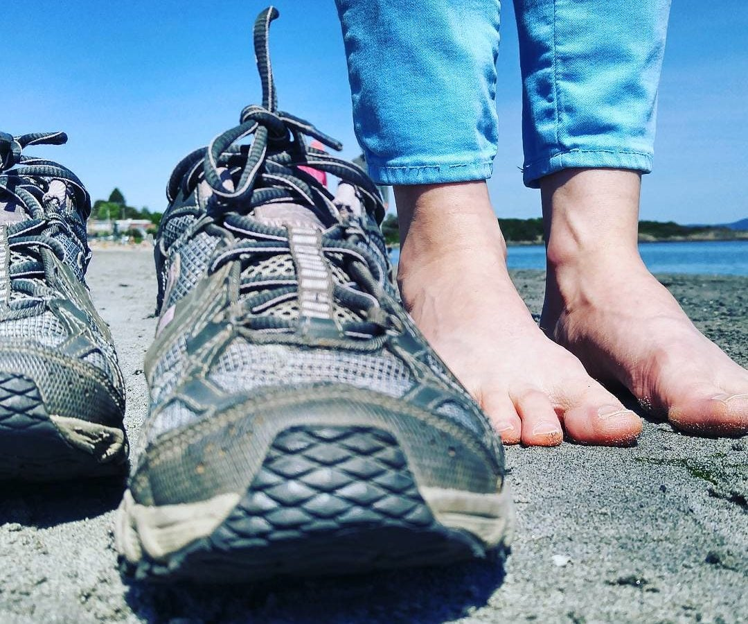 A photo from ground level of a pair of shoes and bare feet on grey sand. The person's pants are bright blue, matching the clear sky and water visible in the background.