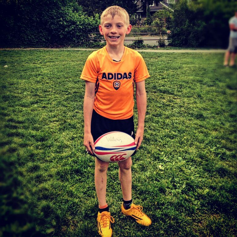 Max stands smiling and relaxed, holding a white rugby ball in both hands. He wears an orange Adidas jersey, standing in front of lush dark green grass.