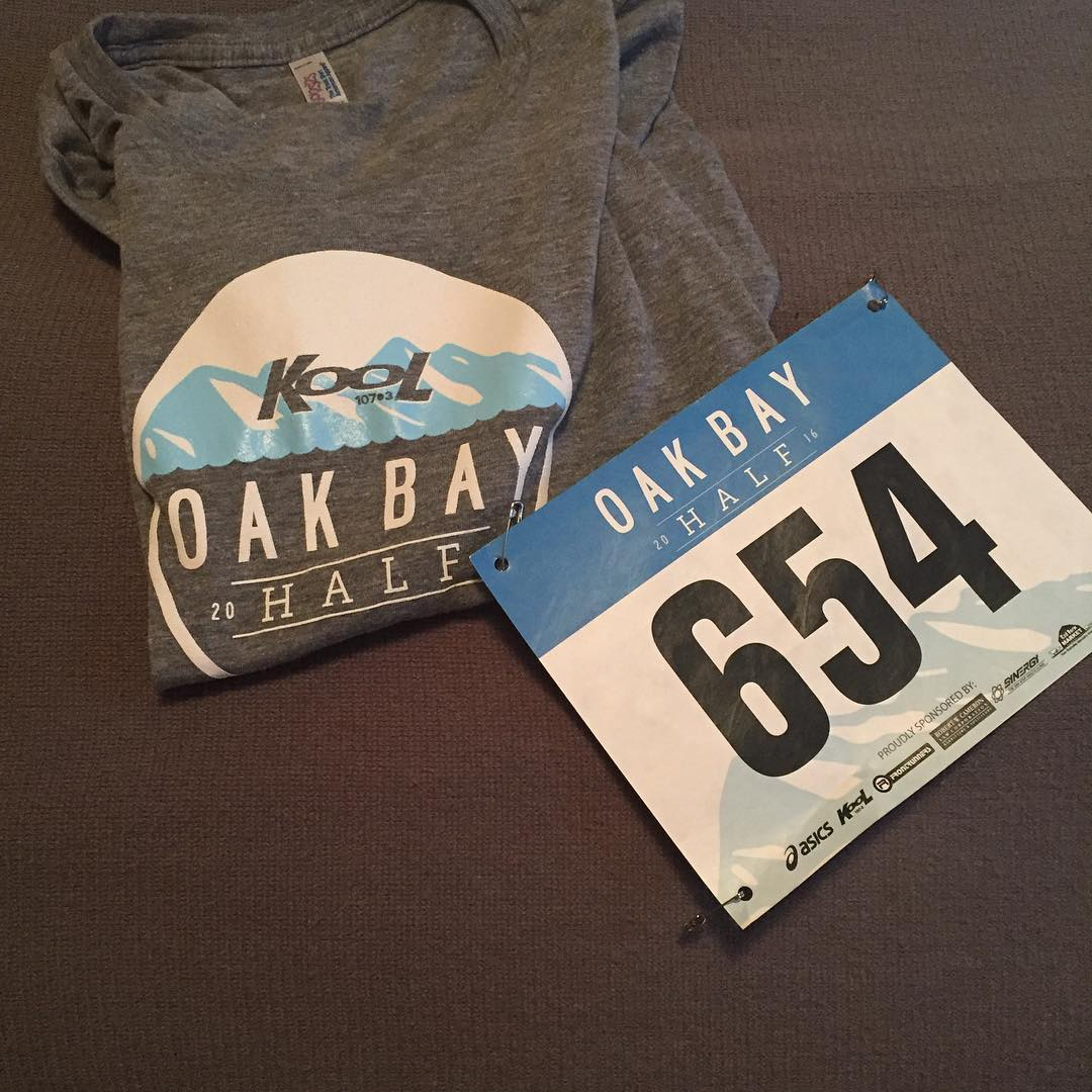 "A folded grey t-shirt with a blue and white design that reads ""Kool 107.3 Oak Bay half"" beside a marathon number bib that reads ""Oak Bay half 654"""