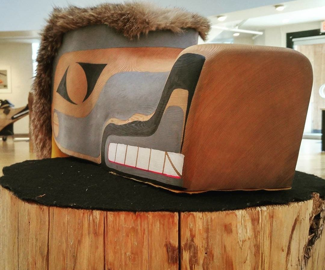 A wooden mask on a raw wooden pedestal. It is a Coast Salish design, with black, white, grey/blue, and red detailing. There is fur on the top and back of the head, and the snout extends 1-2 feet forward.