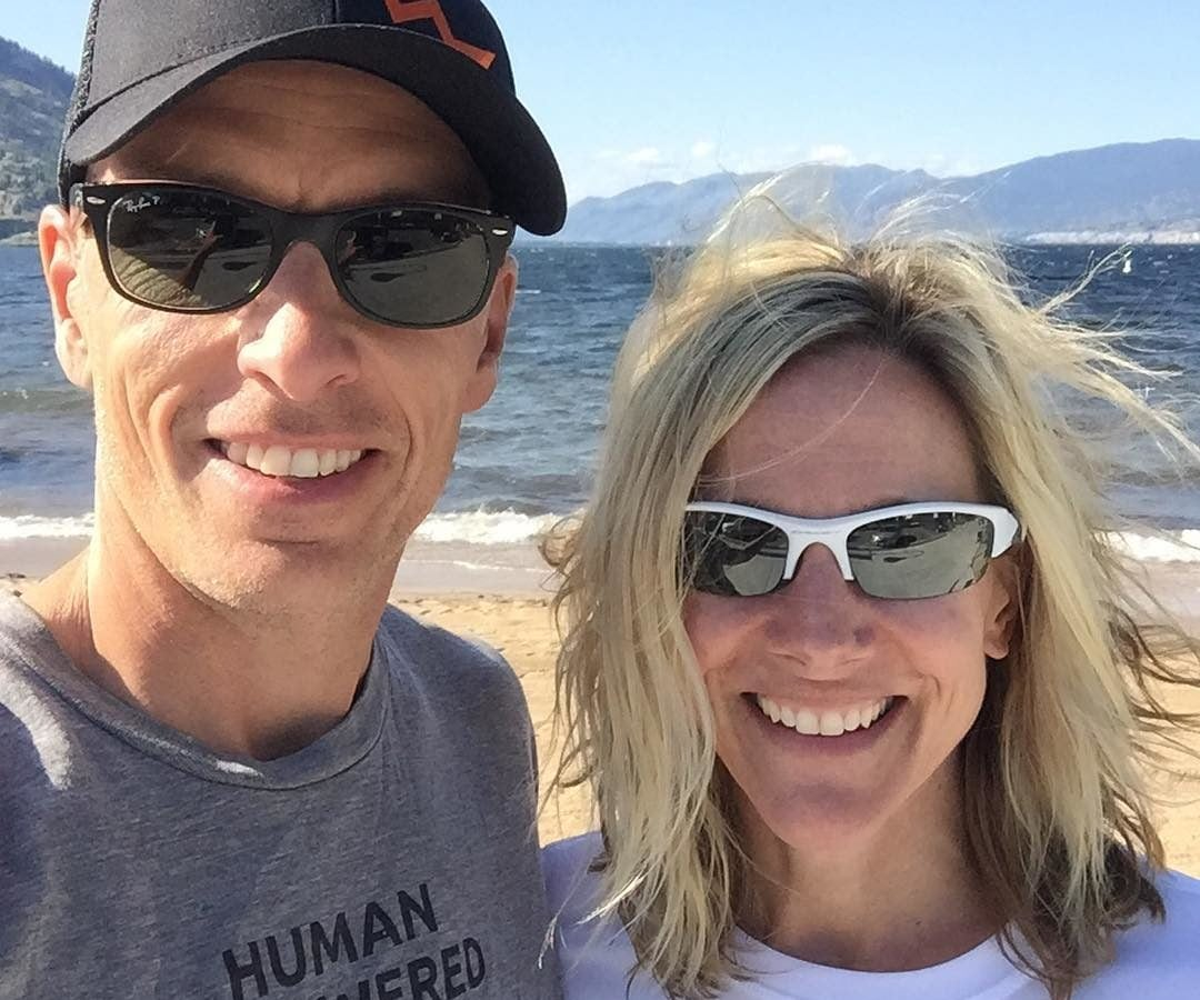 Mike and Sandy smile for a selfie photo. They both wear sunglasses and Human Powered Racing t-shirts. The background is a sandy beach with mountains not far across the water.