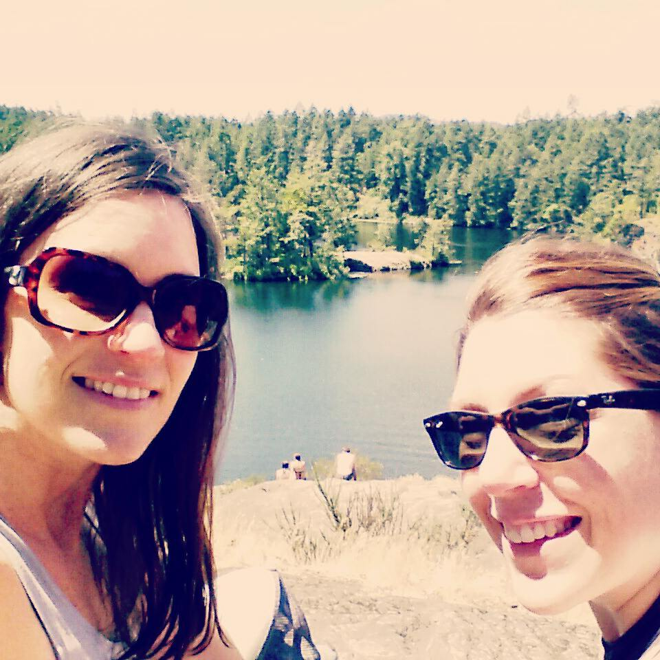 Kristen and Carolyn, both smiling in dark sunglasses, pose for a selfie. Between them is a view of Thetis lake beyond a rocky outcropping, with the forested shore visible across the water.