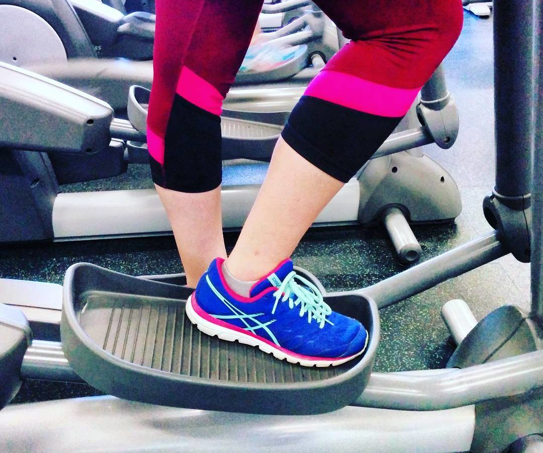 A photo of a woman from the knee down, in bright pink leggings and purple sneakers, on a stair climber machine at the gym. The identical grey machines continue through the background.
