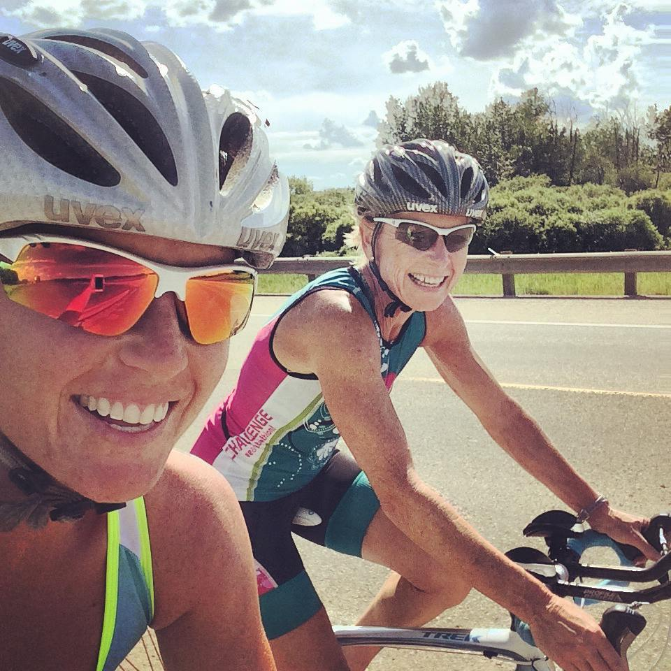 A selfie photo of Sophia and Deb on bikes, wearing helmets, reflective sunglasses and biking athletic-wear, with some asphalt, greenery, and cloudy blue skies visible in the background.
