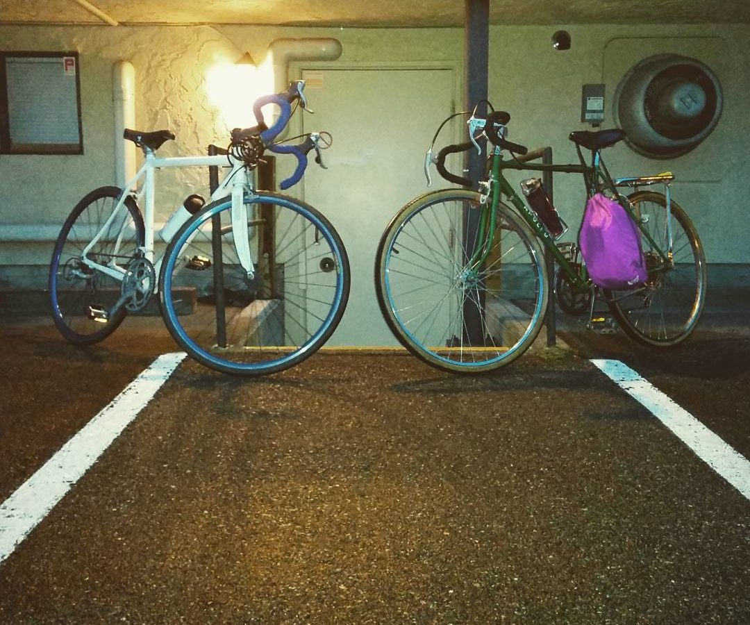 Two bikes parked outside a building at night.
