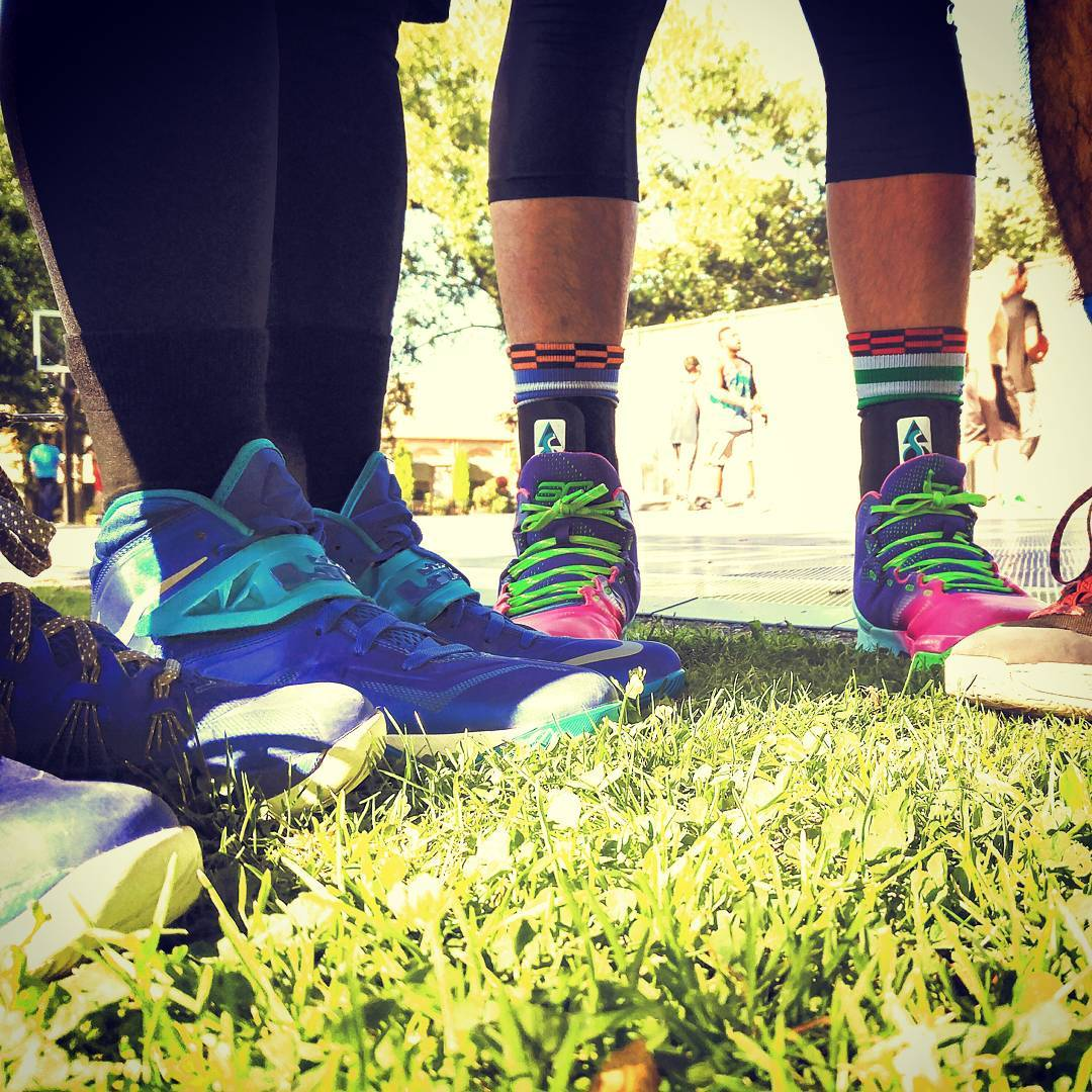 A photos of a few pairs of feet in athletic shoes on grass, with some athletes and a basketball hoop out of focus in the background.