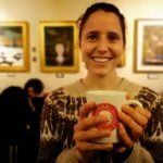 Person in a warm sweater holding a mug that says Yonni's Donuts, in a warmly lit room with paintings hanging in the background, out of focus.