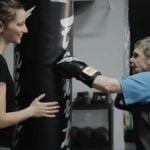 Donna punches a punching bag with one of her gloved hands while Naomi, her physiotherapist, holds the bag steady and smiles encouragingly.