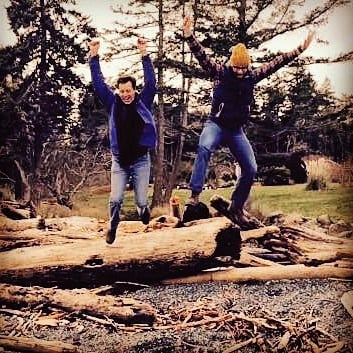 Two people in jeans and light jackets with their arms raised over their heads are jumping up and over a log. Both are smiling. In the foreground are rocks, which suggest a rocky beach, and in the background there is grass, and evergreen trees, and a bright grey sky.