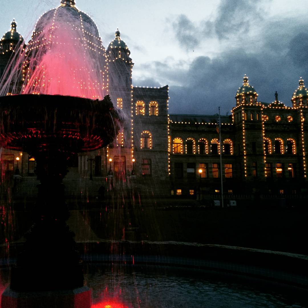 The focus is a fountain, which is lit up with red, and it is to the left. In the background and slightly out of focus is the BC Legislature. This is a large grey stone building with a teal metal roof. It is also lit up with white lights. The sky behind the Legislature is grey with dark clouds.