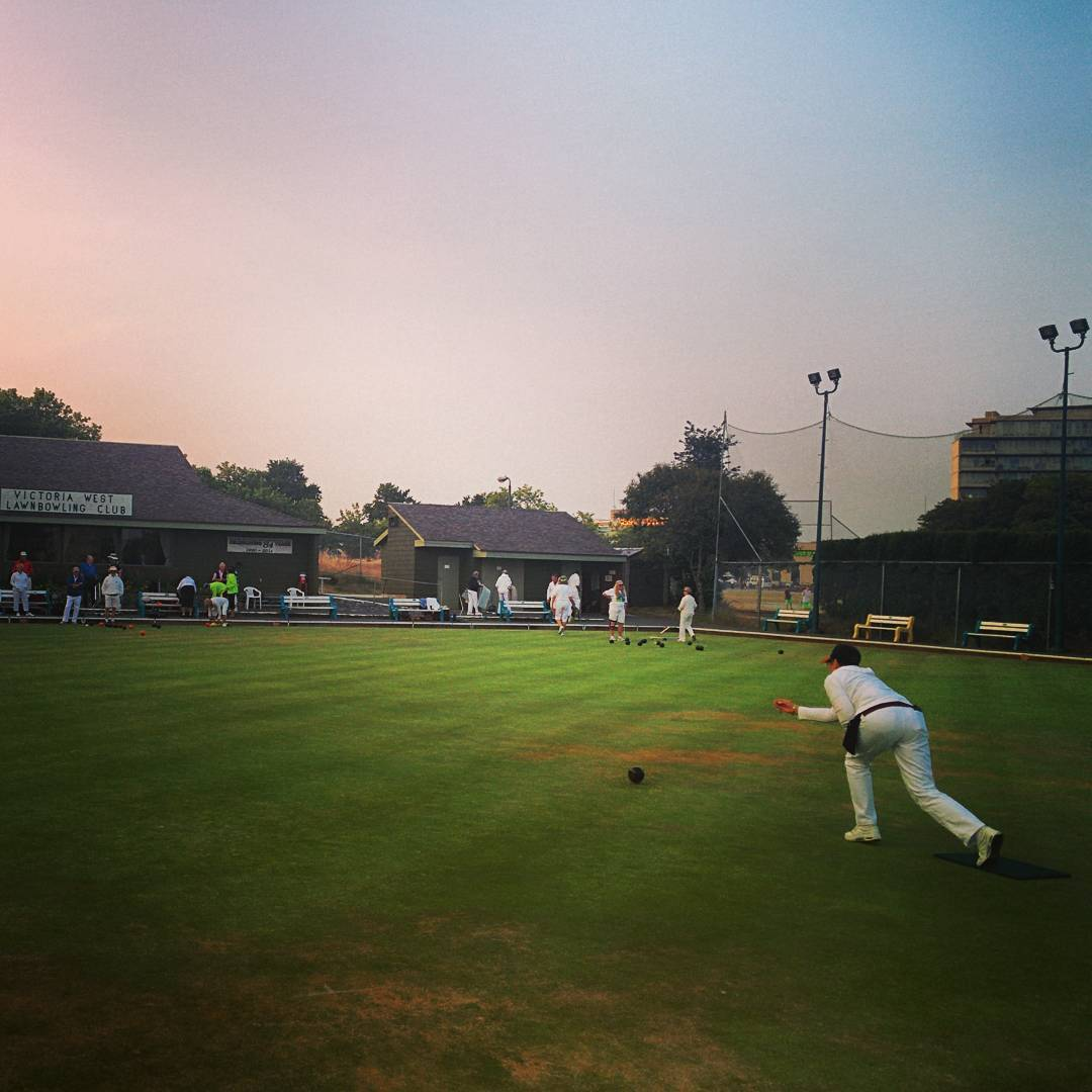 A lawn bowler in a white uniform has just released the black ball and it's rolling down the green field. The thrower is right of center, and in the distance are green trees and a pink sky that fades to blue in the upper right.