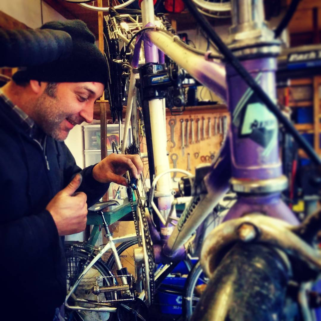A man on the left in a black sweater and black tuque is working on purple bicycle, which is oriented with its front close up to the camera. It is taken indoors.