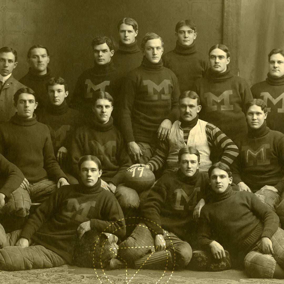 A group of men who look mostly in their 20s arranged for a group photo in 4 tiers. Most of them are wearing sweaters with a capital letter M on the chest. It is an old monochrome photo that is overall a brown colour.