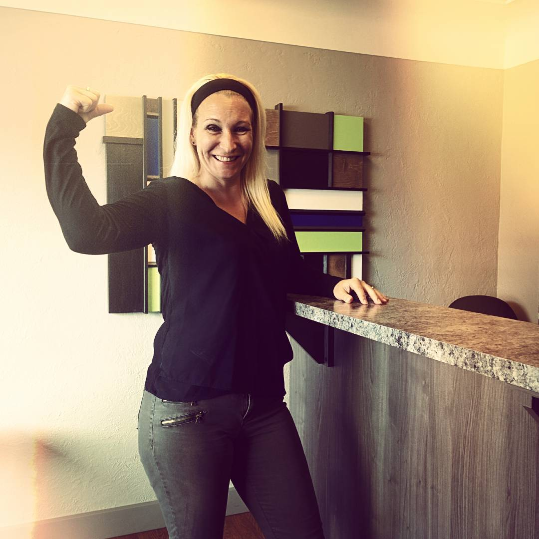 A woman standing in an office with brown walls with her left arms on a bar like counter and her right arm flexed. She is smiling, has long black hair, darkwash jeans, and a long sleeved black shirt.