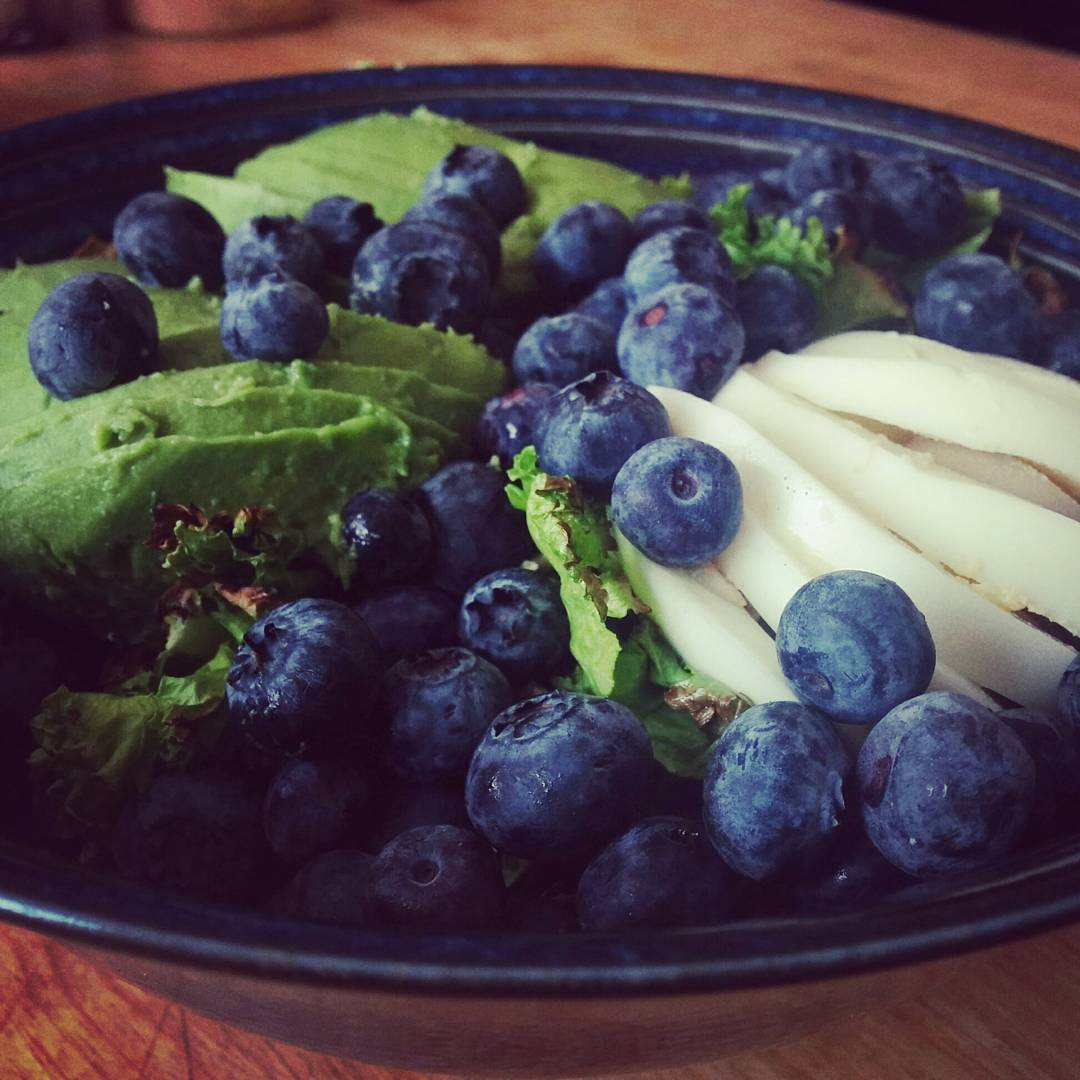 A close up of a black plate on a reddish wooden table. The plate is heaped with avocado, blueberries, pear, and kale which is peaking through from underneath everything else.