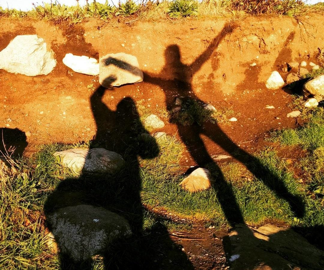 Two people's shadows on a wall of red soil that is topped with grass. There is also grass and red soil on the ground below this natural wall. The person on the left has their left arm raised, and seems to be taking the photo with their right hand. The person on the right is jumping and spreading their arms and legs like a starfish.