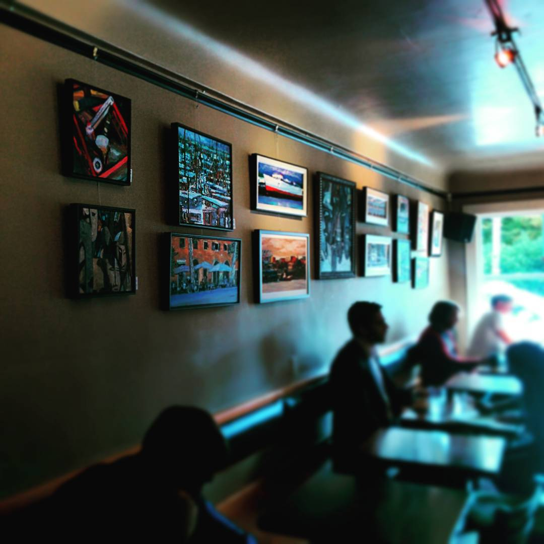 A coffee shop full of people is mostly out of focus. It gets more in focus in the upper left, and there are paintings along the left wall. Light comes from indoor lighting on the ceiling and a window at the far end of the shop.
