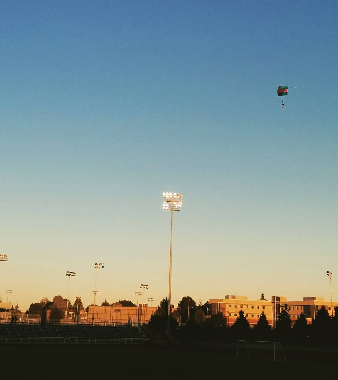 A soccer field at dusk with rectangular buildings in the distance. The sun is setting so the horizon still has some sun but the upper part of the sky is dusky blue, and there is a skydiver with their parachute pulled descending from the upper left.