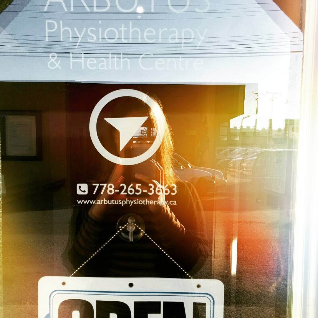 "A woman is reflected in a glass door taking a photo. The door says ""Arbutus Physiotherapy"" in white letters as well as having their logo of an arrow in a white circle and their number (778-265-3663) and website (https://www.arbutusphysiotherapy.ca/) printed in white. There is also an open sign in the door near the bottom of the photo."